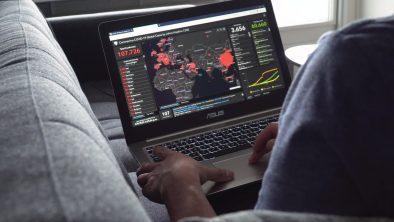 Using laptop with world map of coronavirus